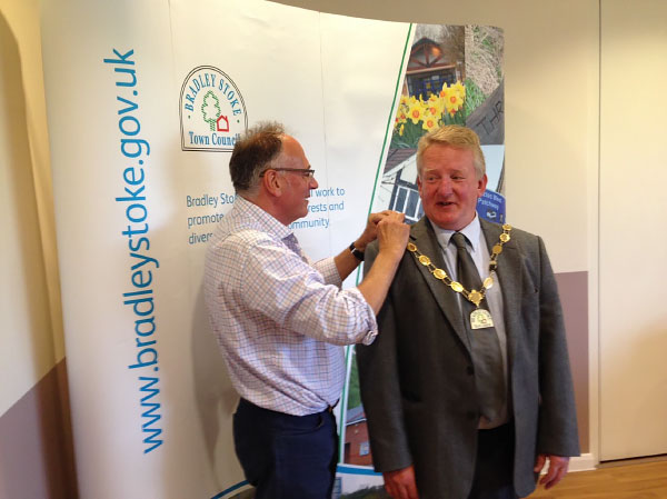 The outgoing Mayor Councillor Brian Hopkinson presents the Chains of Office to the New Mayor Councillor John Ashe.